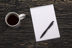 Notebook with pen and mug  on wooden table Royalty Free Stock Photo