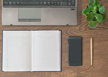 Notebook with pen, notebook and flower on a wooden table. Stock Photos
