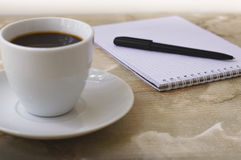 Notebook with pen for notes and black coffee Stock Photos