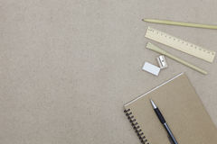 Notebook with pen and pencil eraser on brown paper background. Stock Photography