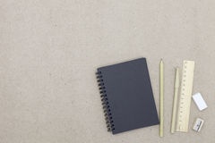 Notebook with pen and pencil eraser on brown paper background. Stock Image