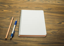 Notebook with pen and pencil. On wood background royalty free stock photo