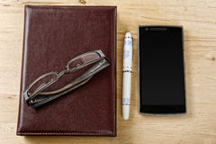 Notebook, pen and phone with blank screen on the table Royalty Free Stock Photos