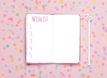 Notebook and pen on pink confetti background. Study arrangement, making wish list or plans. Flat lay, top view. Blogger`s still life Royalty Free Stock Photo