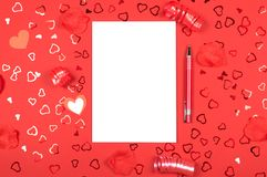 Notebook with pen on red background with heart-shaped confetti royalty free stock photography