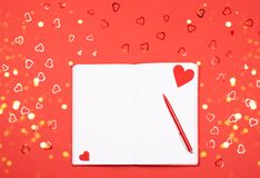 Notebook with pen on red background with heart-shaped confetti stock images