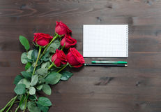 Notebook pen and red roses on  table Royalty Free Stock Images