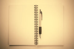 Notebook and pen on sepia colour background Royalty Free Stock Images