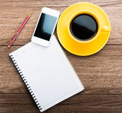 Notebook with pen, smart phone and coffee cup Royalty Free Stock Photo