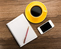 Notebook with pen, smart phone and coffee cup Royalty Free Stock Photography