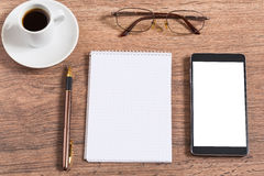 Notebook with pen, smart phone and coffee cup Stock Photography