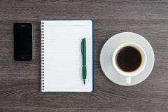 Notebook, pen and Smartphone with cup of coffee Stock Image