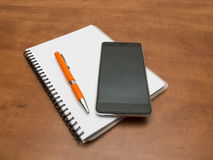 Notebook, pen and smartphone Royalty Free Stock Images