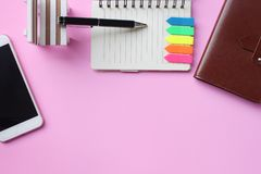 Notebook pen and smartphone are placed on a pink floor and have stock photo