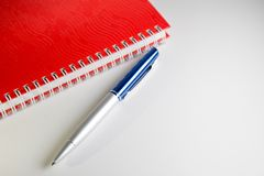 Notebook And Pen. A spiral notebook and a blue pen stock illustration