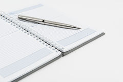 Notebook with pen. A pen on a spiral notepad, isolated in white Stock Image