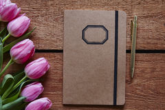 Notebook and pen spring atmosphere with pink tulips.  Royalty Free Stock Photos