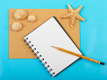 Notebook with pen and starfish and seashells, isolated on blue b. Ackground Stock Images