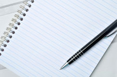 Notebook with pen on table Stock Image