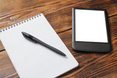 Notebook with pen, tablet/e-reader on wood table. Notebook with pen and tablet/e-reader on old wood table Stock Photos