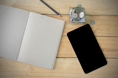 Notebook, Pen, Tablet, Stack Coins on wooden table form top view. Stock Photography