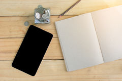 Notebook, Pen, Tablet, Stack Coins on wooden table form top view. Royalty Free Stock Photo