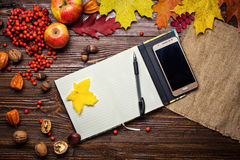 Notebook, pen and telephone in autumn still life, fall leaves, g Royalty Free Stock Photo