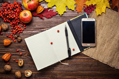 Notebook, pen and telephone in autumn still life, fall leaves, g Royalty Free Stock Photography