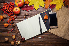Notebook, pen and telephone in autumn still life, fall leaves, g Royalty Free Stock Images
