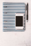 Notebook with pen and telephone on the white table vertical Royalty Free Stock Image