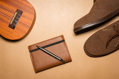 Notebook, pen , ukulele and boots on a brown paper background Stock Photos