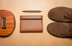 Notebook, pen , ukulele and boots on a brown paper background Stock Photography