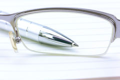 Notebook and Pen,View through glasses. Isolated over white Royalty Free Stock Photos