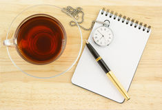 Notebook with pen, watch and tea Stock Photography
