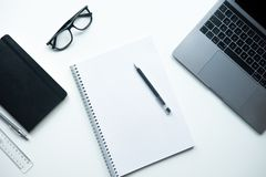 Notebook with pen on white background . Office table with laptop, notebook, glasses royalty free stock photo