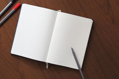 Notebook and pen on wood background. Notebook is open and pen on wood background Royalty Free Stock Photography