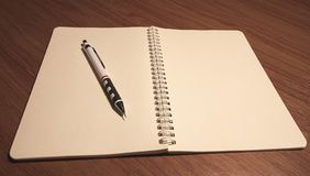 Notebook and pen on wooden . stock images