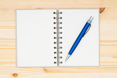 Notebook and pen on wooden surface Stock Photography