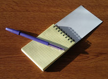 Notebook and pen on the wooden table Stock Images