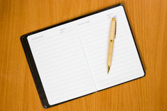 Notebook and pen on the  wooden table Royalty Free Stock Photo