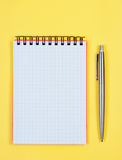 Notebook with pen on yellow background. Royalty Free Stock Photo