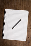 Notebook and pencil. On wooden table Royalty Free Stock Photos