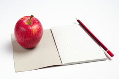 Notebook, pencil and apple Stock Images