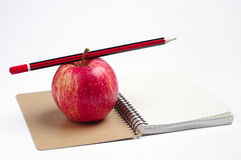 Notebook, pencil and apple Stock Image