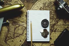 Notebook, pencil, camera, compass, coin, wallet, airplane on blur vintage world map, journey concept, copy space, retro tone. Notebook, camera, pencil, compass Royalty Free Stock Photos