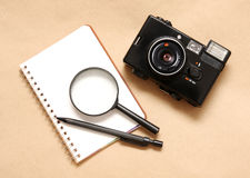 Notebook with pencil and camera,magnifying. Notebook with pencil and camera on brown paper,magnifying Stock Photography