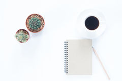 Notebook with pencil coffee cup and cactus on white Royalty Free Stock Photos