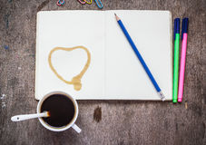 Notebook with pencil, colored pens, paperclip and coffee Royalty Free Stock Photography
