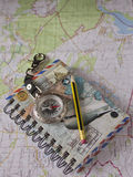 Notebook, pencil and compass lying on a topographic map.  stock photography