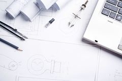 A notebook, a pencil, a compass and rolls with drawings on the table in the architect. Design and working drawings with pencils, rule and compasses royalty free stock photography